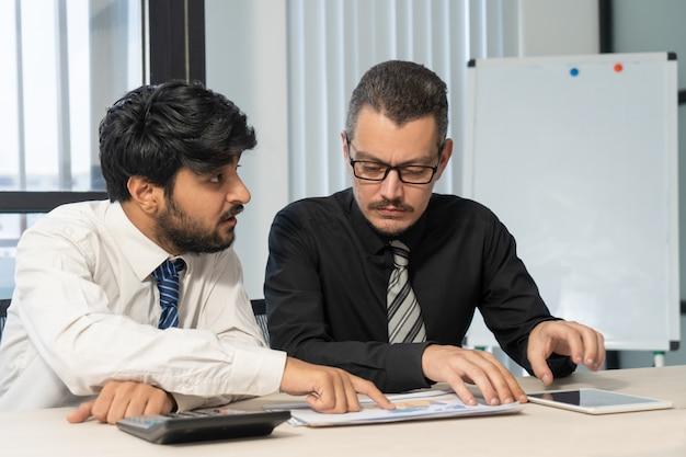 Un expert financier indien montrant du papier tout en expliquant les données.