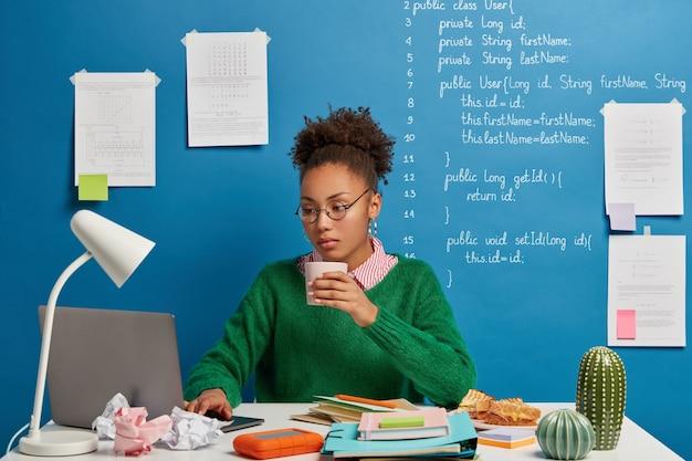 Une experte en programmation sérieuse travaille sur un projet indépendant dans un espace de coworking, boit du café, porte des lunettes rondes et un pull vert.