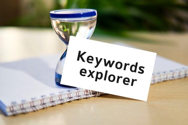 Explorateur de mots-clés - texte de concept de référencement d'entreprise sur un cahier blanc et une horloge de sablier, feuilles vertes de fleurs