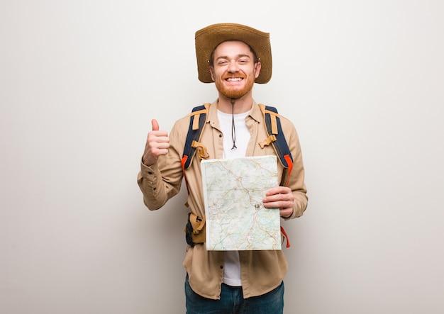 Explorateur rousse jeune homme souriant et levant le pouce vers le haut