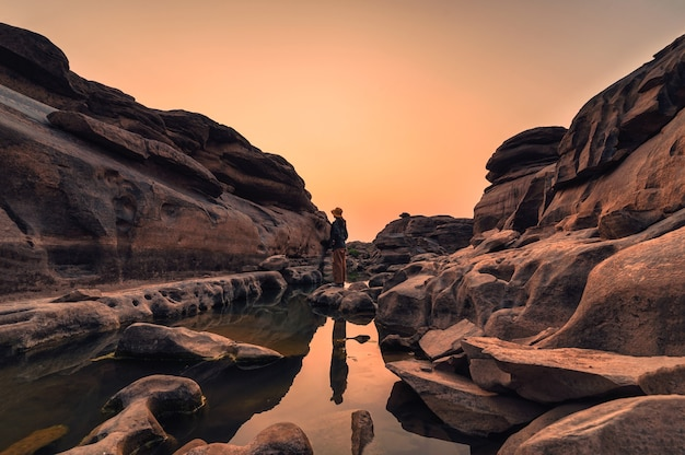 Exploratrice femme debout dans de grands rapides rocheux dans la soirée à hat chom dao