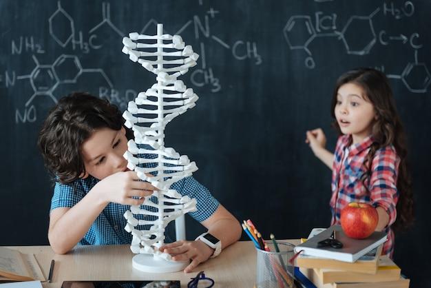 Explorer l'évolution du génome. crafty impliquait des enfants qualifiés assis à l'école et profitant d'un cours de chimie tout en écrivant au tableau et en utilisant une tablette