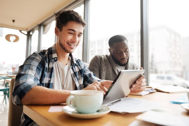 Explorer le nouveau contenu faible angle de jeune beau mec souriant à l'aide d'un ordinateur portable pendant que son ami est occupé à prendre des notes au café.