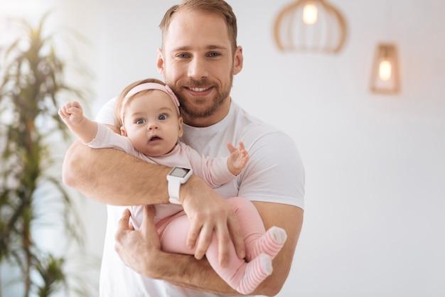 Explorer tout autour. drôle mignon bébé joyeux fille couchée dans les mains du père et regardant ailleurs tout en exprimant son intérêt et sa joie