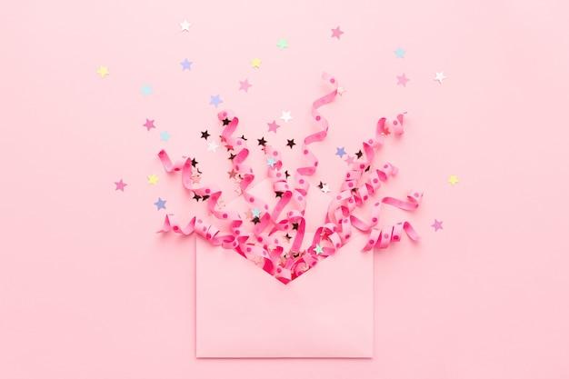 Explosion de confettis de banderoles et d'étoiles pastel de l'enveloppe.