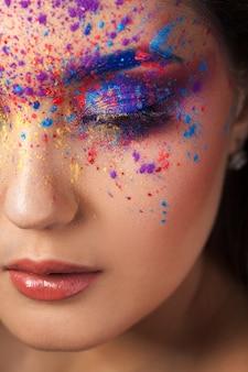 Explosion de couleurs, ombres multicolores éparpillées sur les paupières. yeux smokey colorés et sourcils bleus.