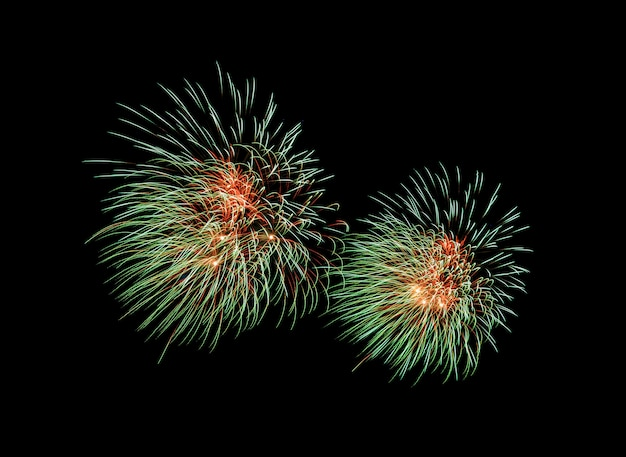 Explosion de feux d'artifice vert et rouge sur le ciel nocturne