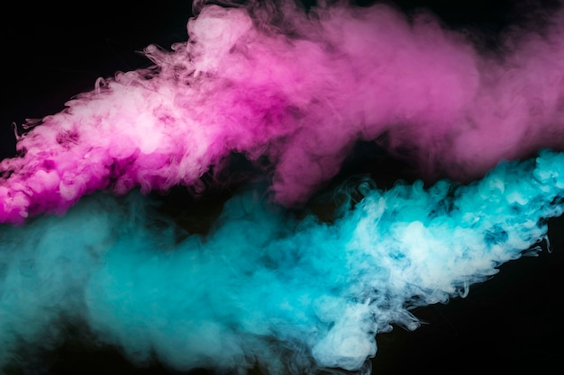Explosion de fumée bleue et rose sur fond noir
