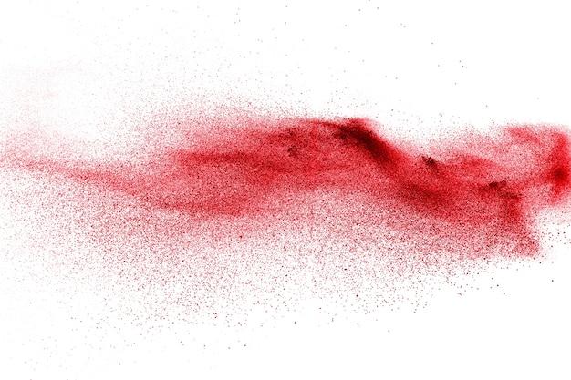 Explosion de particules de poussière rouge sur fond blanc.
