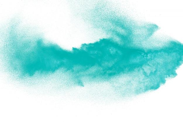 Explosion de particules de poussière verte sur fond blanc.