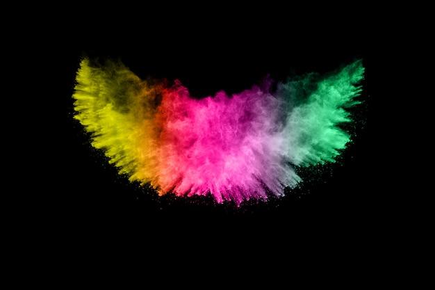 Explosion de poudre abstraite multi couleur sur fond noir. figer le mouvement de la poussière de couleur s