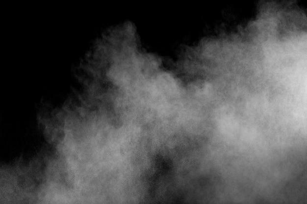 Explosion de poudre blanche isolée sur fond noir. éclaboussures de particules de poussière blanche.
