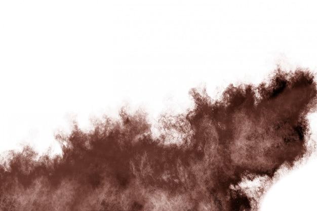 Explosion de poudre de couleur brune sur fond blanc.