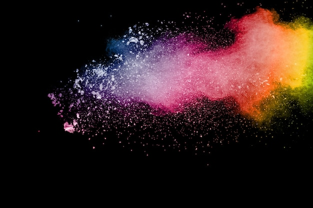 Explosion de poudre de couleur. éclaboussure de poussière colorée isolée sur fond noir.