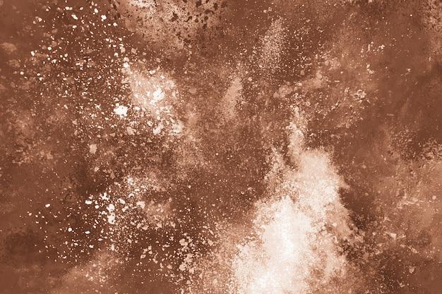 Explosion de poudre de couleur marron sur fond blanc.