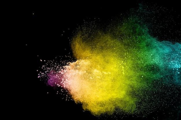 Explosion de poudre multicolore abstraite sur fond noir. les particules de poussière de couleur éclaboussent.