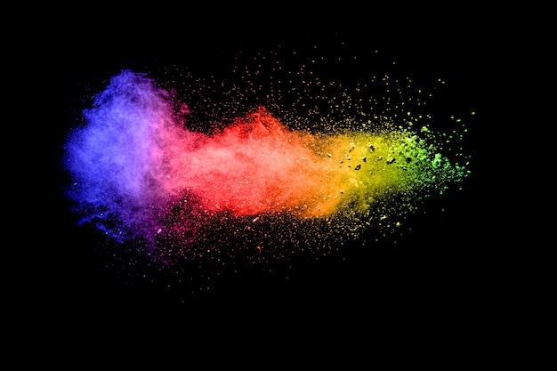Explosion de poudre multicolore sur fond noir.