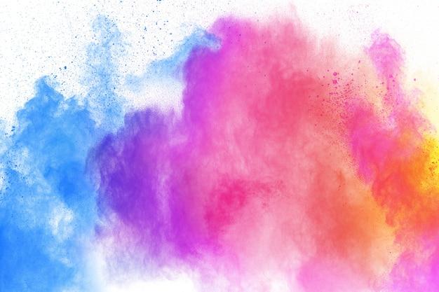 Explosion de poudre multicolore. lancé des particules de poussière colorées éclaboussant.
