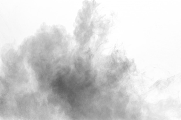 Explosion de poudre noire sur fond blanc. les particules de poussière de charbon expirent dans l'air.