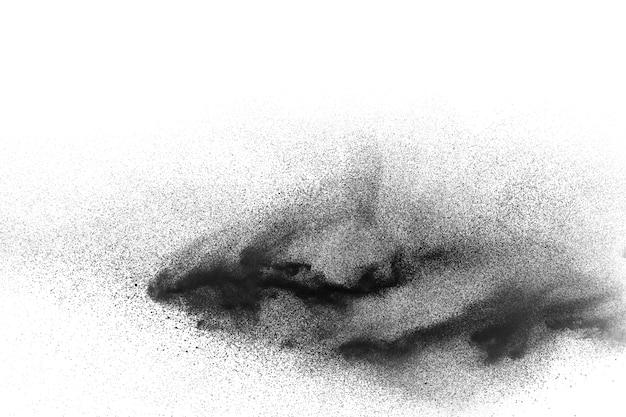 Explosion de poudre noire sur fond blanc particules de poussière noire éclaboussant.