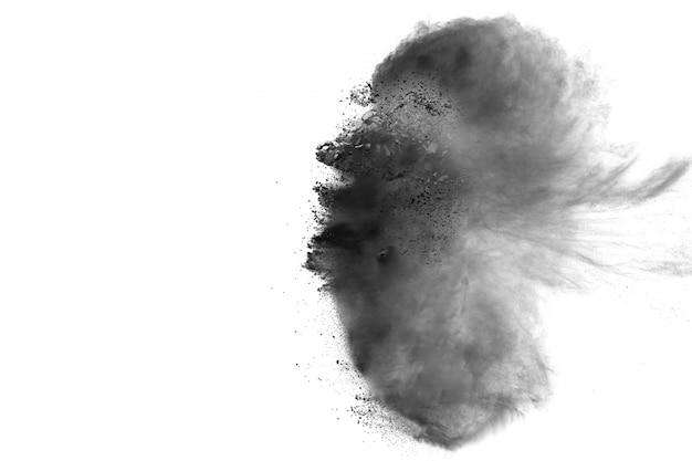 Explosion de poudre noire sur fond blanc. des particules de poussière noire éclaboussent.