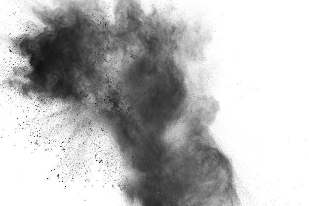 Explosion de poudre noire. gros plan de particules de poussière noire éclabousser isolé sur fond.