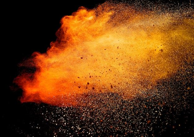 Explosion de poudre orange isolée sur fond noir
