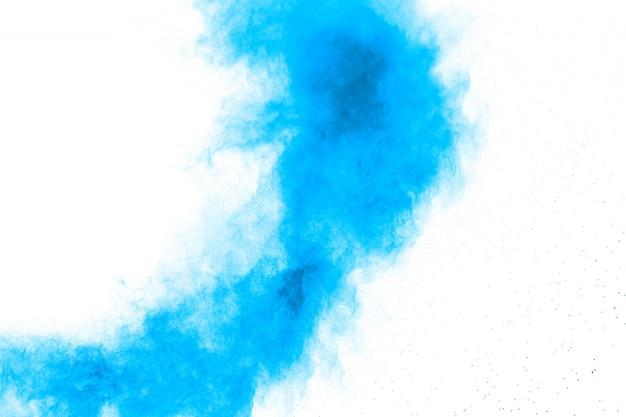 Explosion de poussière bleue abstraite sur fond blanc. figer le mouvement des éclaboussures de poudre bleue.