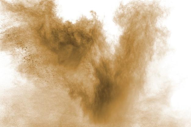 Explosion de poussière brun foncé abstraite sur fond blanc.