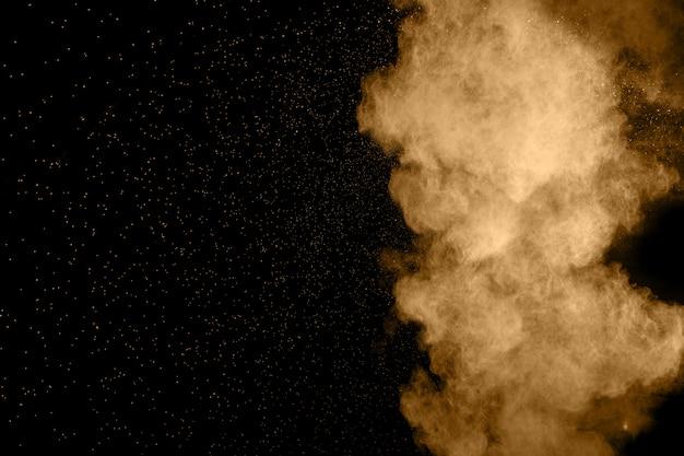 Explosion de poussière brune abstraite sur fond noir.