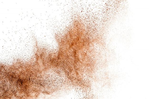 Explosion de poussière de poudre brun foncé sur fond blanc.