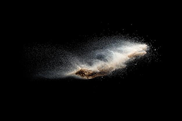 Explosion de sable isolée sur fond noir. figer le mouvement des éclaboussures de poussière de sable.