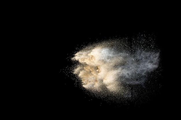 Explosion de sable de rivière à sec. éclaboussure de sable doré sur fond noir.