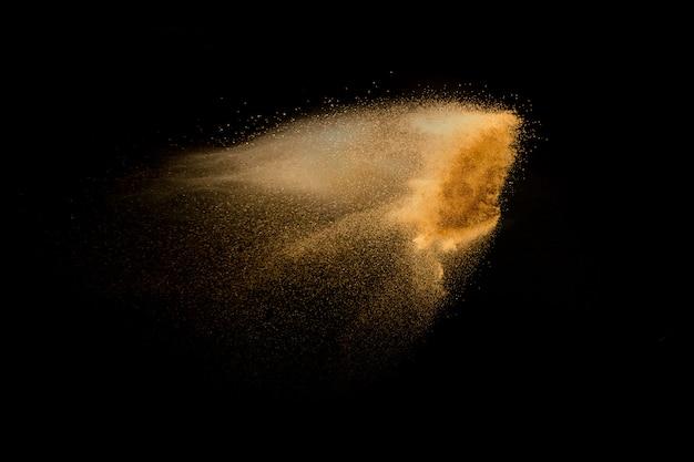 Explosion de sable de rivière à sec isolée sur fond noir. nuage de sable abstraite. éclaboussure de sable couleur brun sur fond sombre.