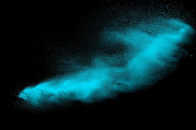 Explosion de sable vert isolée sur fond noir.