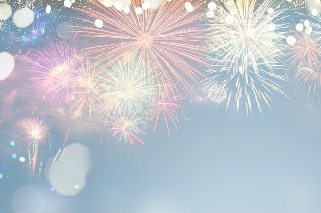 Explosions colorées de feux d'artifice sur fond bleu et festif avec espace de copie