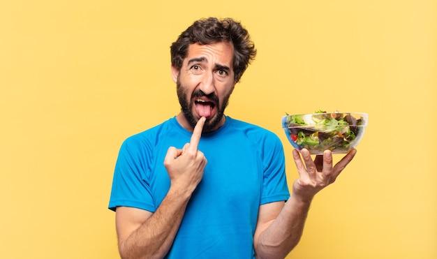 Expression en colère de jeune athlète barbu fou, tenant la salade