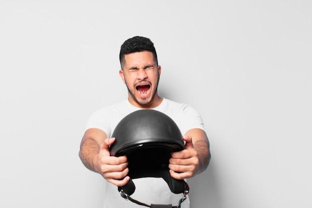 Expression en colère de jeune homme hispanique. concept de motard