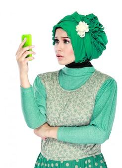 Expression confuse ou choquée en regardant un téléphone mobile