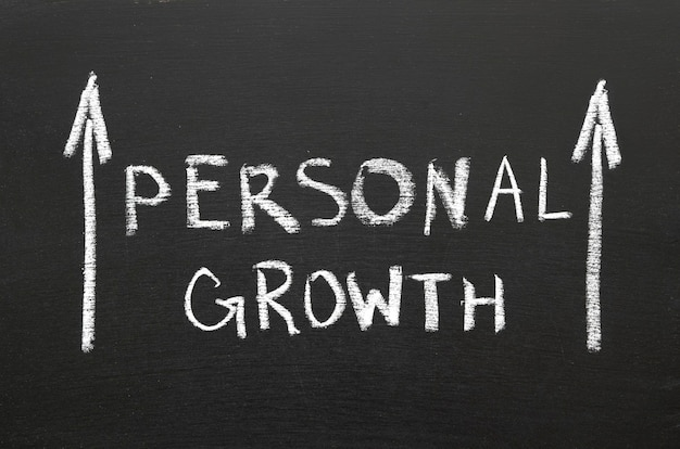 Expression de croissance personnelle manuscrite sur le tableau avec des flèches montantes