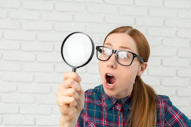 Expression drôle. choqué femme regardant à travers une loupe.
