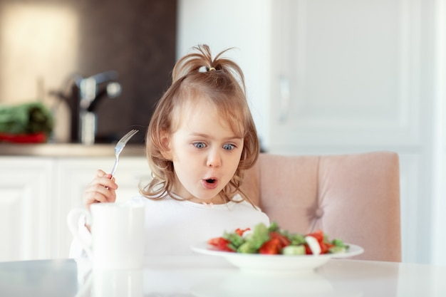 Expression émotionnelle enfant fille mangeant des légumes crus frais salade de vitamines dans la cuisine blanche.concept d'une alimentation saine pour les enfants