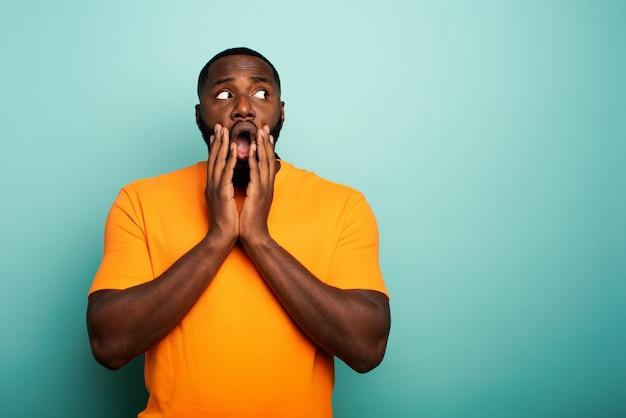 Expression étonnée et choquée d'un garçon noir sur cyan