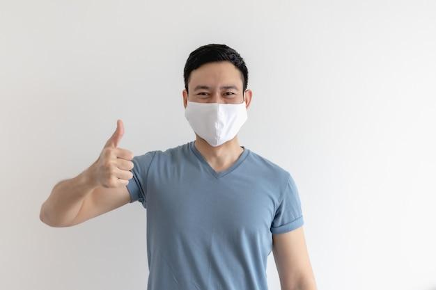 Expression heureuse et heureuse de l'homme au masque blanc sur un mur isolé.