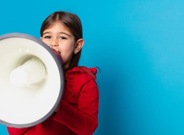 Expression heureuse de jolie petite fille et tenant un mégaphone