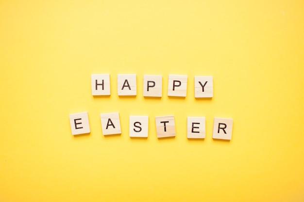 Expression joyeuses pâques faites de blocs de bois sur un jaune clair
