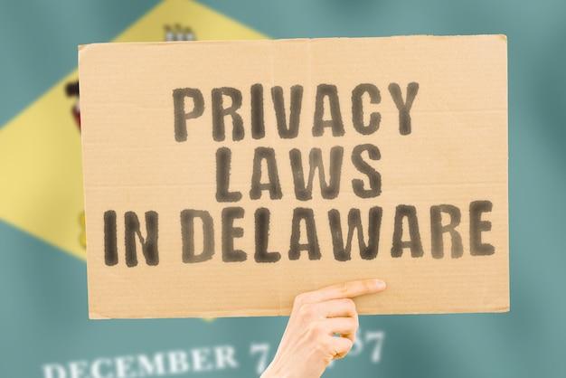 L'expression lois sur la protection de la vie privée au delaware sur une bannière dans la main des hommes avec un drapeau finlandais flou