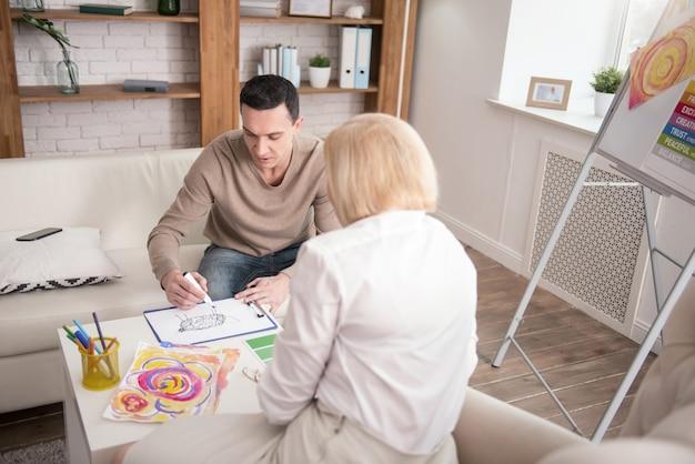 Expression de soi. vue de dessus de l'homme méditatif visitant une psychologue lors de l'utilisation du marqueur