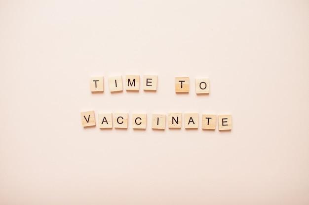 Expression de temps pour vacciner en blocs de bois sur un rose clair