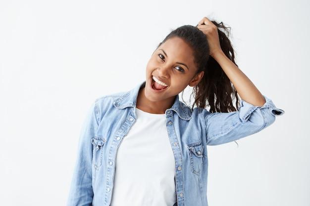 Expressions et émotions du visage humain. portrait de jeune femme brune afro-américaine en chemise en jean bleu clair s'amuser, tenant ses cheveux avec la main, la bouche grande ouverte.
